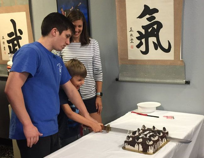 Instructor helps student cut birthday cake with a sword