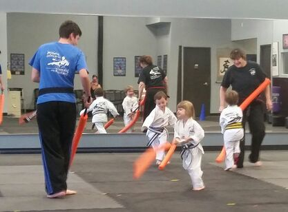 Kids play a karate game with instructors